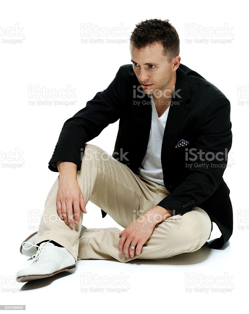 Contrarié décontracté et élégant homme assis et regardant loin - Photo