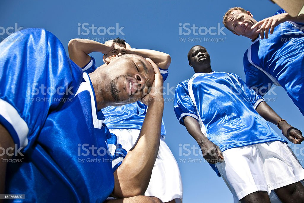 Upset Soccer Players in a Group Huddle During Game stock photo