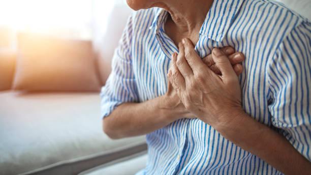 upprörd stressad mogen medelålders kvinna som känner smärta värk vidrör bröstet med hjärtinfarkt - spetsig vinkel bildbanksfoton och bilder