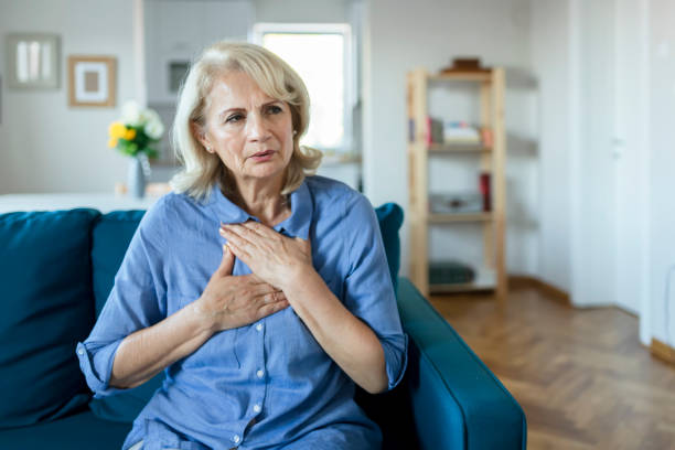 Upset stressed older woman feeling heartache Senior Woman Suffering From Chest Pain While Sitting on Sofa at Home. Old Age, Health Problem, Vision and People Concept. Heart Attack Concept. Elderly Woman Suffering From Chest Pain Indoor chest torso stock pictures, royalty-free photos & images
