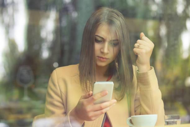 彼女はこぶしを携帯電話で受信したメッセージに怒っている携帯電話を保持している動揺の重点を置かれた女性は、コーヒー ショップ背景を分離しました。悲しい顔表現感情気持ち身体言語を探して - 羨望 ストックフォトと画像