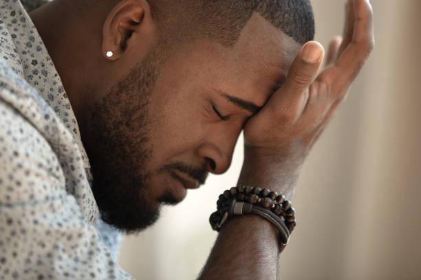 upprörd stressad ung afrikansk amerikansk man hantera stark huvudvärk - led bildbanksfoton och bilder