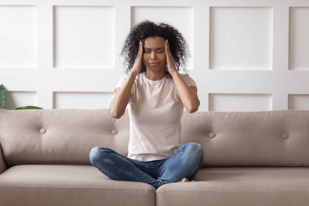 Upset stressed young african woman massage temples feel strong headache Upset stressed young african woman massage temples feel strong headache concept, frustrated tired black girl touching aching head suffer from migraine high blood pressure sitting on sofa at home hormone stock pictures, royalty-free photos & images