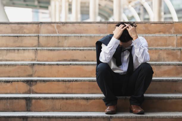 aufgebracht betonte junge asiatische geschäftsmann in anzug mit händen auf dem kopf auf der treppe sitzen. arbeitslosen-und entlassungskonzept. - verzweiflung stock-fotos und bilder