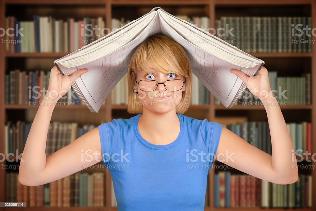 Upset student in library holding open book over her head stock photo