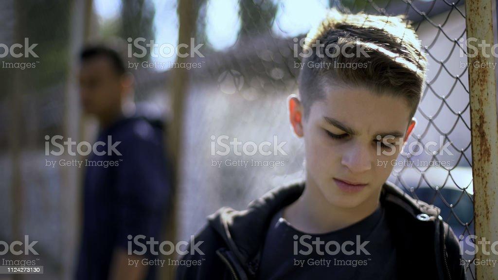 Verärgert Teenie jungen stützte sich auf Metallzaun, aufgegeben mit der Gesellschaft, Waisenhaus – Foto