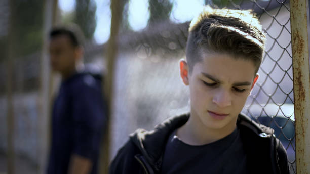 Upset teen boys leaning on metal fence, abandoned with society, orphanage Upset teen boys leaning on metal fence, abandoned with society, orphanage drug abuse stock pictures, royalty-free photos & images