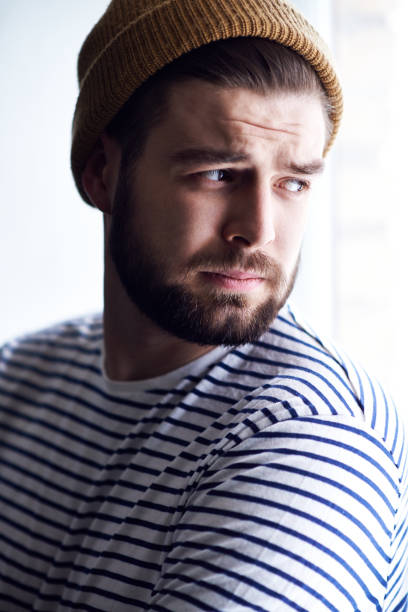 Upset tired young male sailor in beanie hat and stripped sweater frowning forehead and looking out window Upset sailor looking out window sailor suit stock pictures, royalty-free photos & images