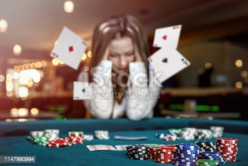 Upset woman in casino with falling cards