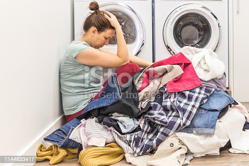 Upset woman in laudry room sitting ona floor with dirty clothes, tired and frustrated