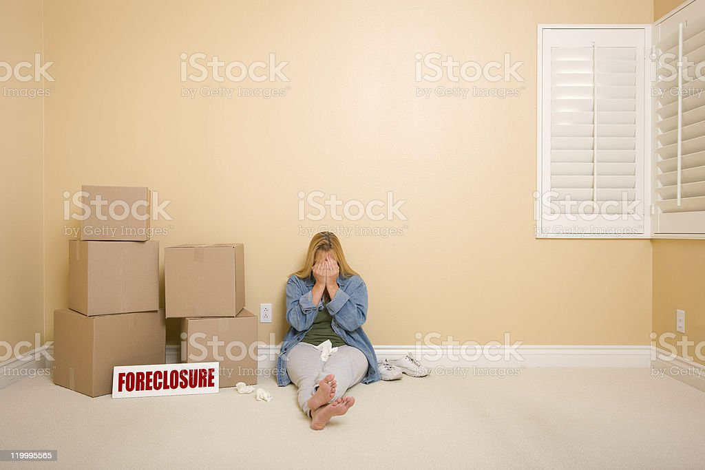 Upset Woman on Floor Next to Boxes and Foreclosure Sign stock photo