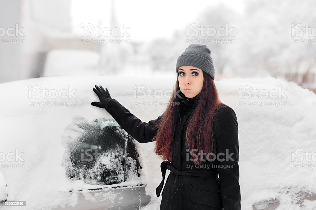 Upset Woman Removing Snow from a Car stock photo