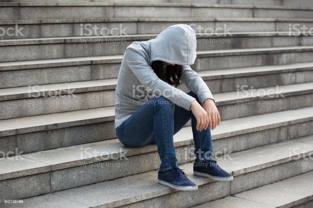 Upset woman sitting alone in city stairs stock photo