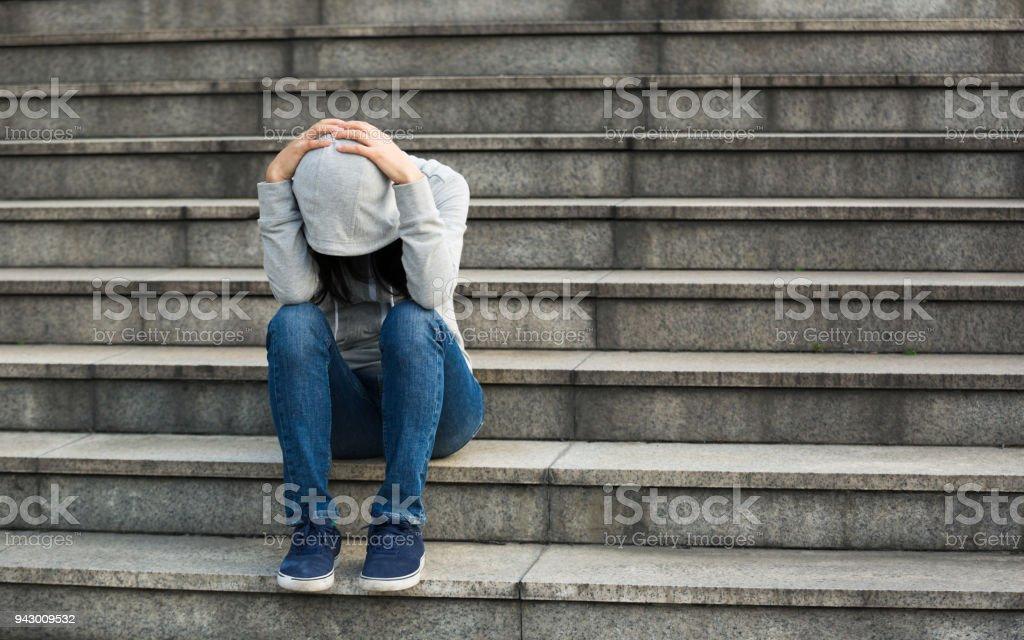 Upset woman sitting alone on city stairs stock photo