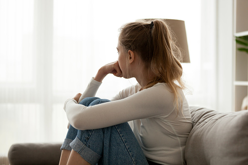 istock Upset woman sitting on couch alone at home 1063392686