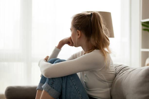 verärgert frau sitzen auf couch allein zu hause - verzweiflung stock-fotos und bilder