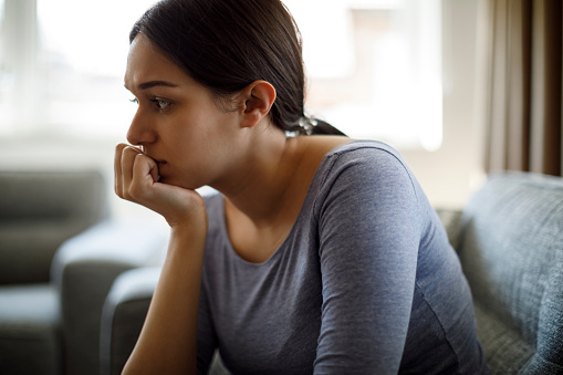 Upset woman sitting on sofa alone at home