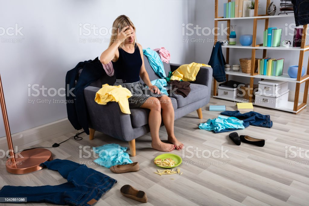 Upset Woman Sitting On Sofa Surrounded By Scatted Clothes