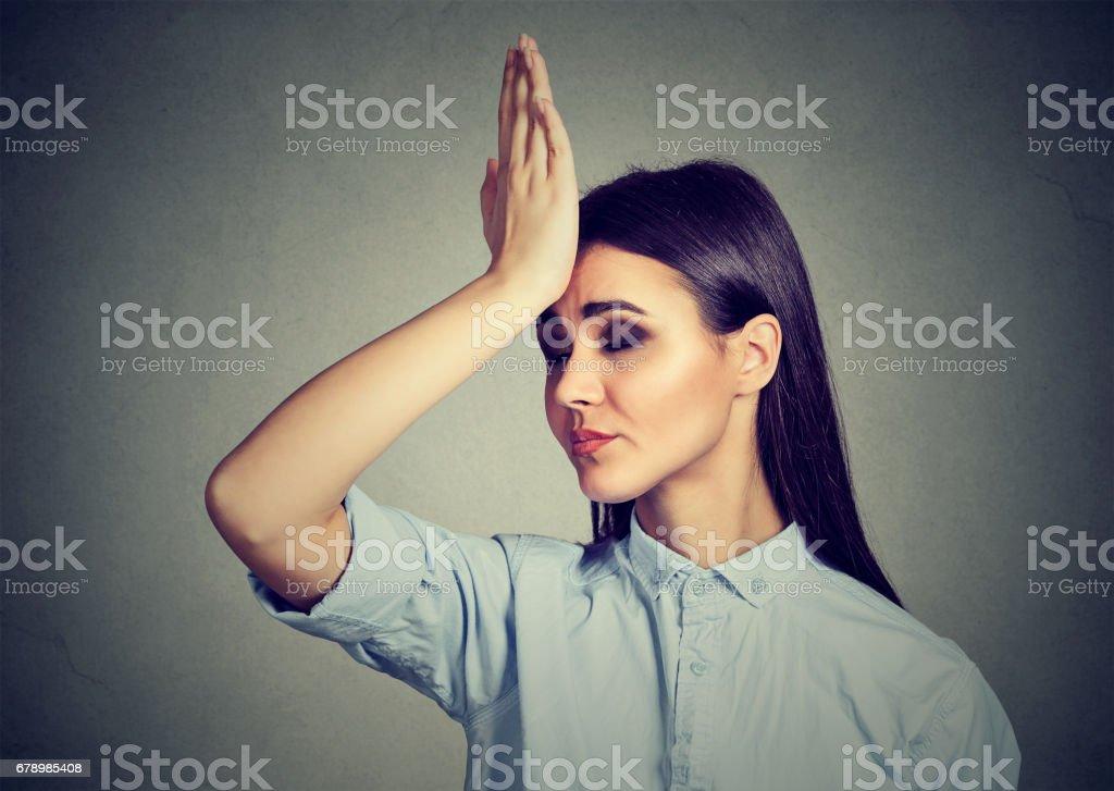 upset woman, slapping hand on head having duh moment stock photo