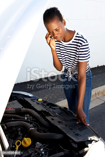 860373412 istock photo upset young african woman standing by  broken down car parked on the side of a road and calling for assistance 944698464