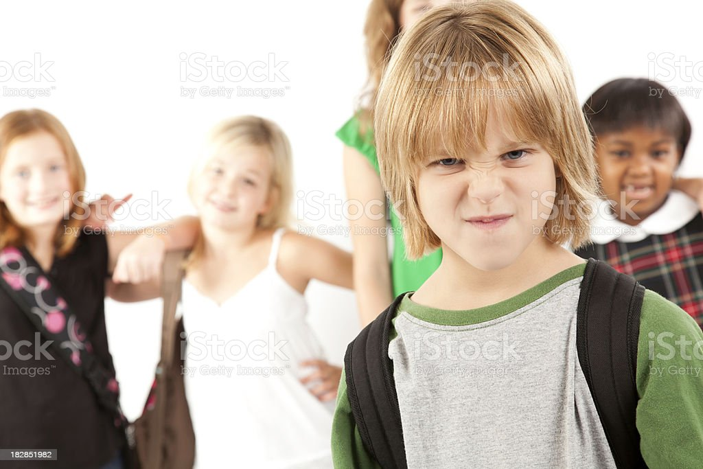 Upset Young Boy In Front of School Classmates stock photo