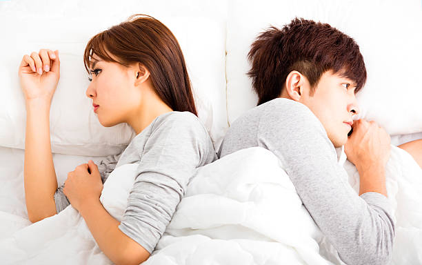 Upset young couple  lying side by side in bed stock photo