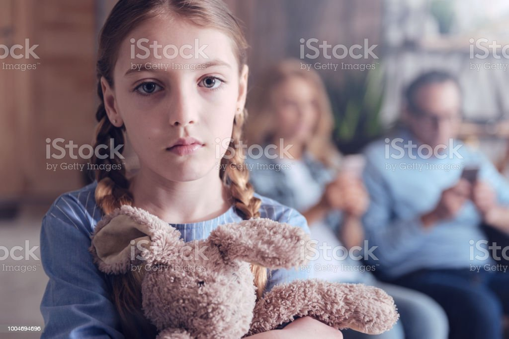 My only friend. Upset pretty young girl hugging her fluffy toy and...