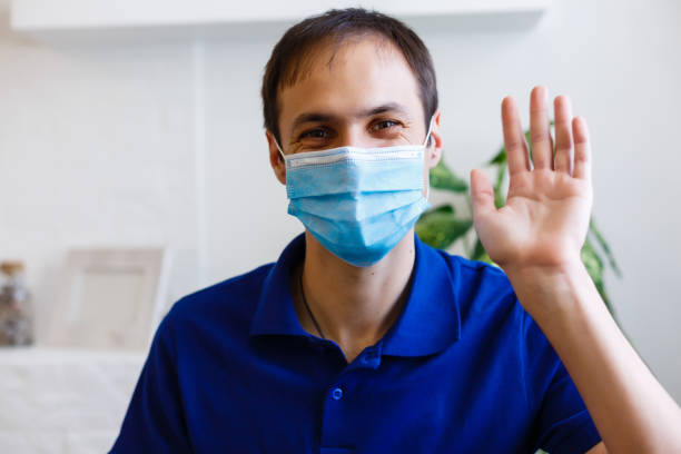 Upset young man in gray sweater, scarf with sterile face mask making video call with mobile phone, spreading hand isolated on grey background. Health, ill sick disease treatment, cold season concept stock photo