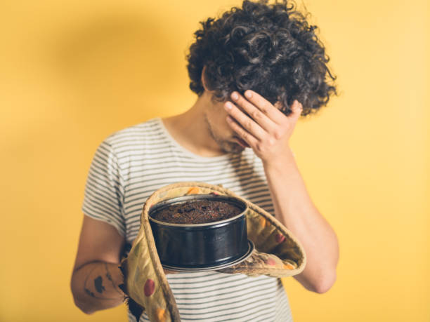 Upset young man with burnt cake stock photo