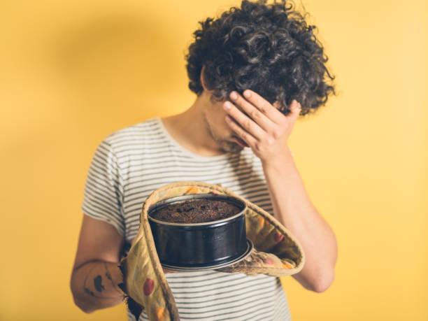 upset young man with burnt cake - burned cooking imagens e fotografias de stock