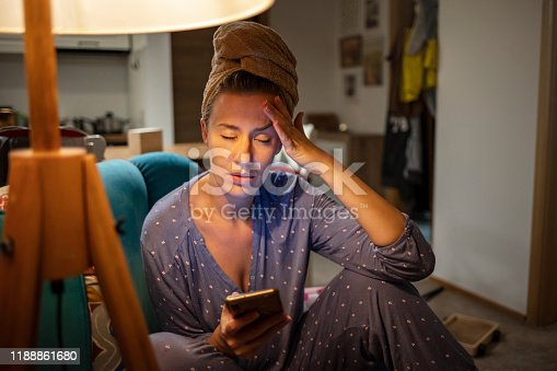 521815364 istock photo Upset young woman sit on couch at home hold smartphone 1188861680