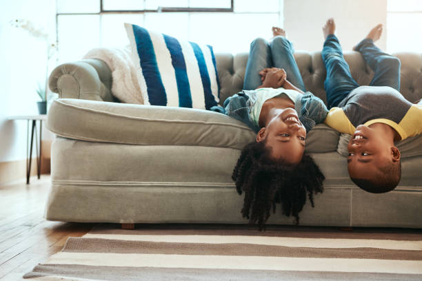 Upside down but doing the right type of fun Shot of a brother and sister hanging upside down off the sofa at home brother stock pictures, royalty-free photos & images