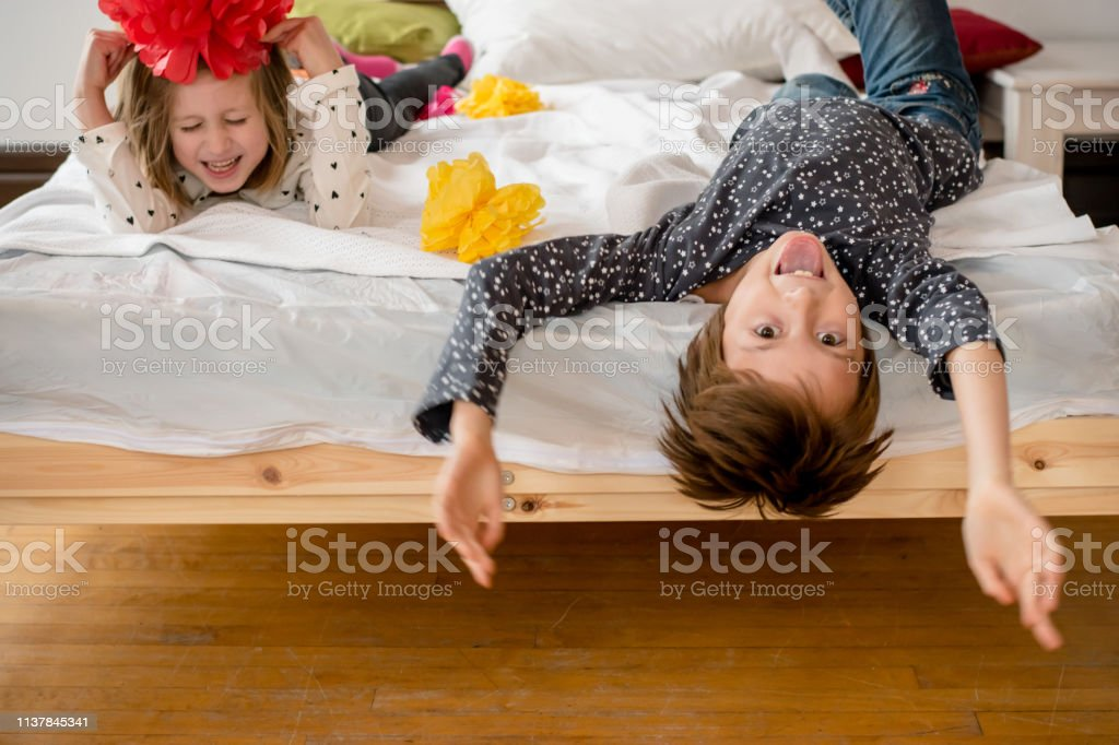two kids are upside down on a bed