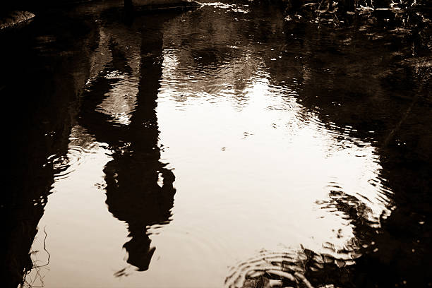 Upside down reflection Reflection of standing man in buggy water. peter pan stock pictures, royalty-free photos & images
