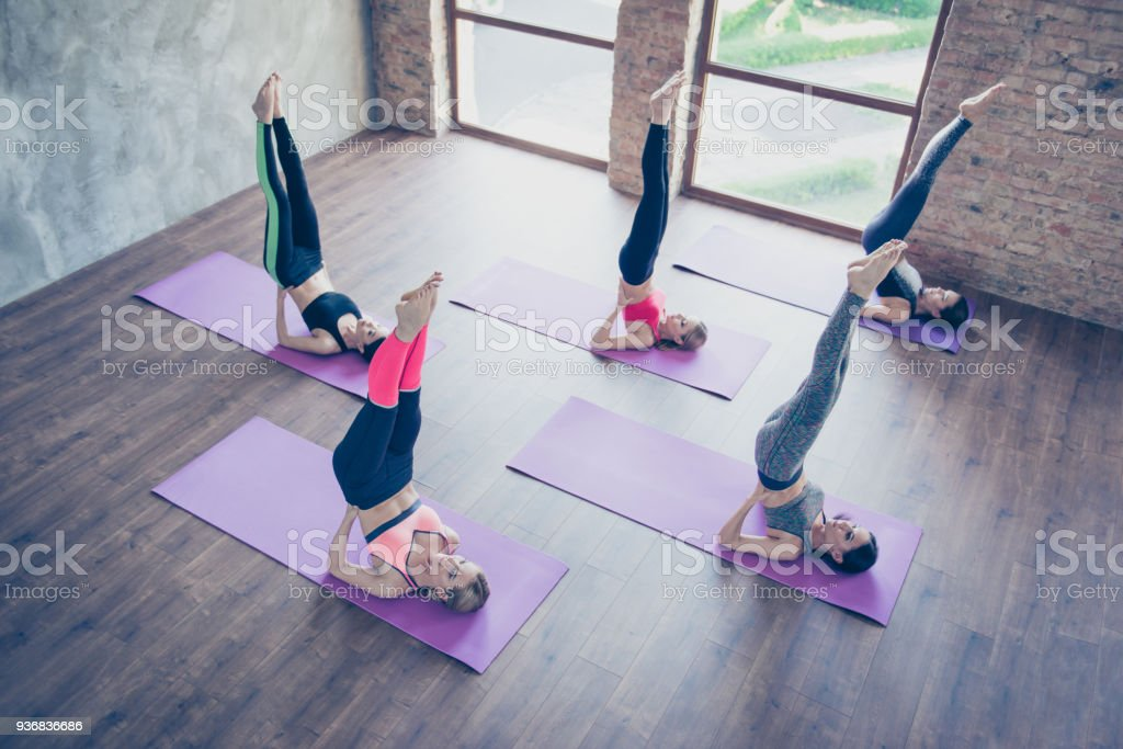 Upside down seal pose. Topview of five pretty young slim ladies,...