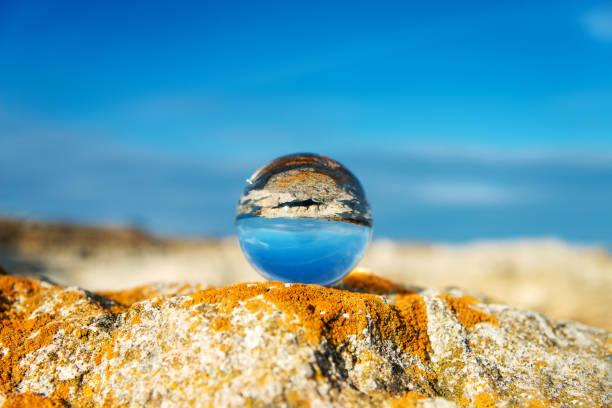 Seelandschaft mit blauem Himmel auf den Kopf und bewachsen mit Moos Felsen - Reflexion in einem Objektiv-Ball - selektiven Fokus, Raum für Text – Foto