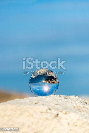 Upside down seascape with blue sky and overgrown with moss rocks - reflection in a lens ball - selective focus, space for text