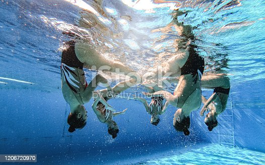 Synchronized swimming athlete group practicing a choreography together in a swimming pool.