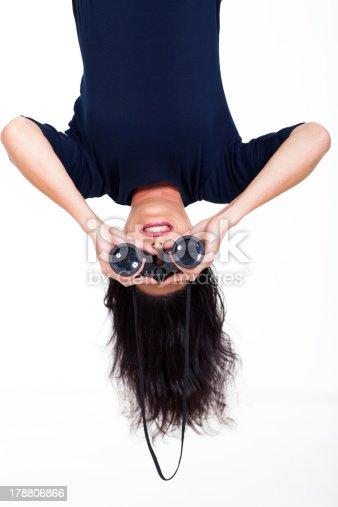 istock upside down woman holding binoculars 178806866