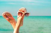 逆さまに女性の足、赤いペディキュア サンダル、海辺でサングラスを着用します。面白いと幸せのファッションの若い女性は、休暇でリラックスします。ビーチで女の子をリラックスできま