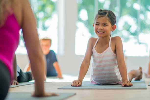 Upward Facing Dog A multi-ethnic group of elementary age children are taking a yoga class together at the gym. They are in upward facing dog. upward facing dog position stock pictures, royalty-free photos & images
