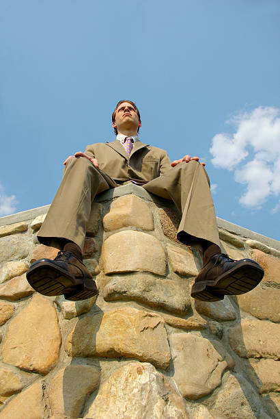 upward shot business man on corner of stone wall - mikefahl stock pictures, royalty-free photos & images