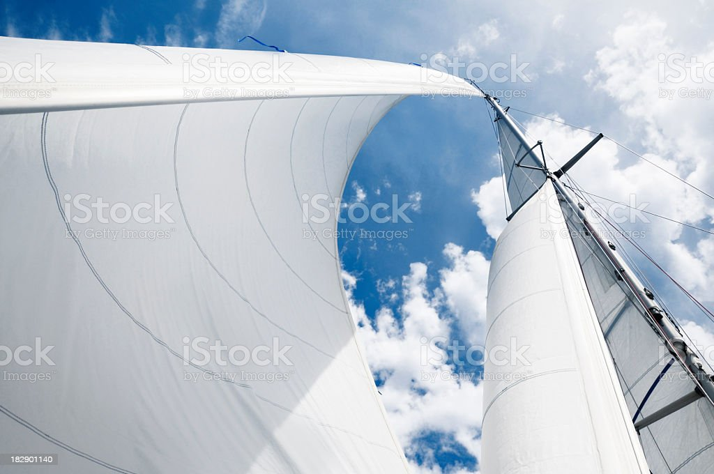 Upward shot of curved white sails against a blue cloudy sky stock photo