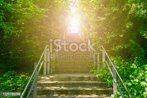 Upward concrete stairs ascending to the brightness of sunlight