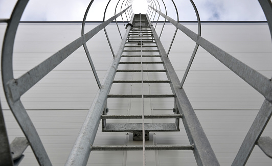 upward view of a fire inspection ladder installed on the wall of a building or on chimneys. has a guide rope for tying the rope of the climber's belt. protective grille galvanized metal gray tunnel, chimney sweep cleaning, climbing a ladder, firefighter,
