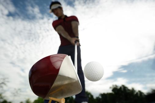 Upward view of a golfer mid golf swing