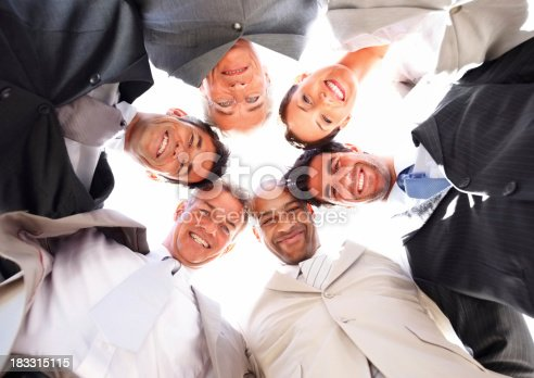 465474428istockphoto Upward view of business people with heads together on white 183315115