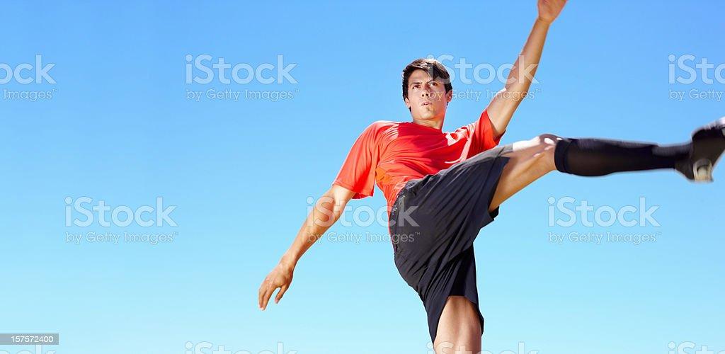 Upward view of pro footballer taking a shot royalty-free stock photo