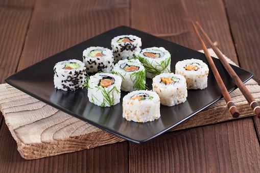 Hossomaki ou Uramaki: essa imagem traz nove uramakis em um prato preto quadrado. Apoiado no prato, há um hashi.