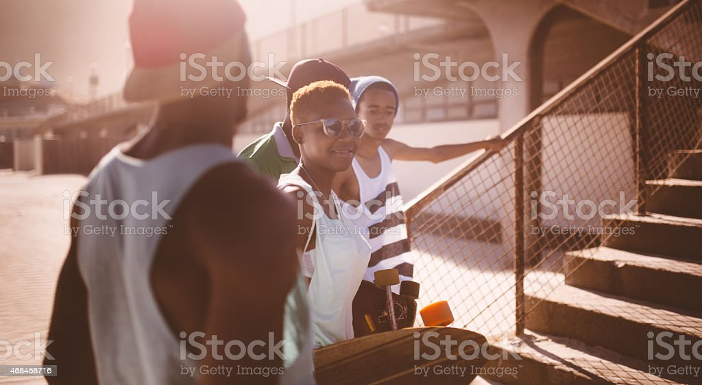 Urban African American students happily talking in a friendly group stock photo